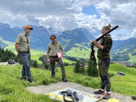 Bild 1 - Der St.Galler Wildhüter Sepp Koller und Jagdaufseher René Schläpfer prüfen eine Jungjägerin im Fach Waffenhandhabung.