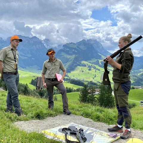 Bild 1 - Der St.Galler Wildhüter Sepp Koller und Jagdaufseher René Schläpfer prüfen eine Jungjägerin im Fach Waffenhandhabung.. Vergrösserte Ansicht